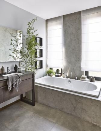 Také koupelna dokonale odráží zenovu náladu prostředí, je velmi útulná, ale střídmá. Betonová stěrka je kombinovaná s velkoformátovou dlažbou imitující beton. Jejich surovost zjemňuje dřevěný nábytek, sladěné doplňky a rostliny v asijském duchu. K většímu komfortu přispívá i vana pro dvě osoby