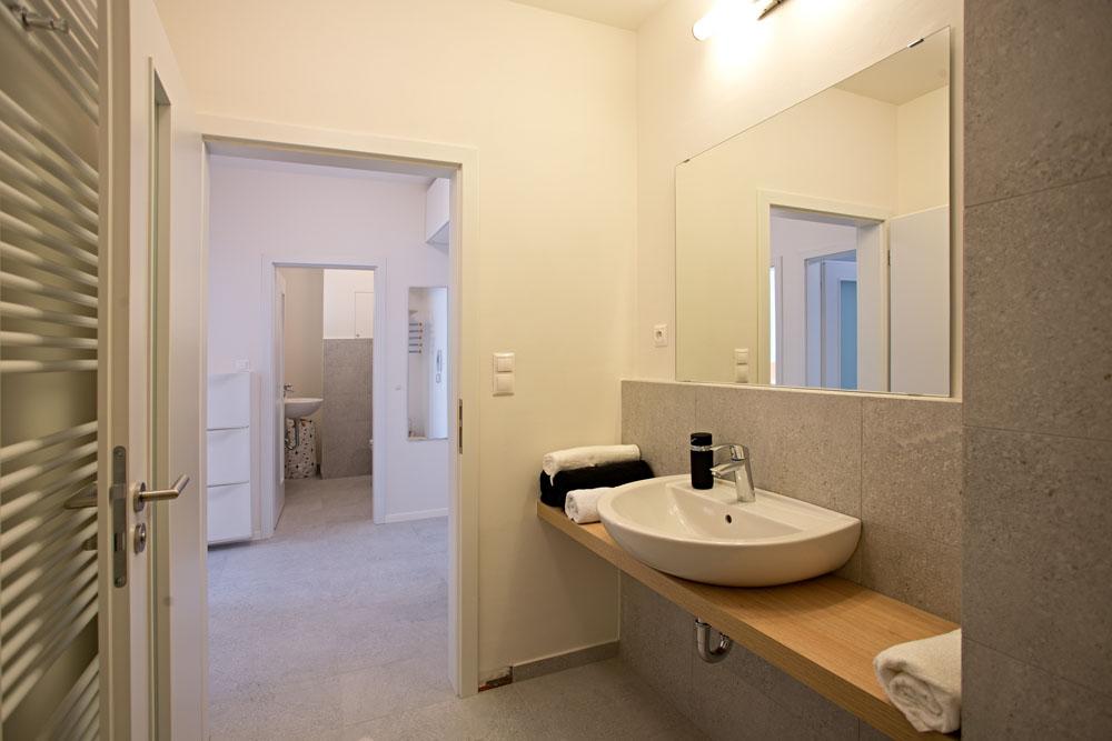 Průhled z koupelny přes předsíň do místnosti s WC, umývadlem a pračkou potvrzuje vzdušnost celého bytu