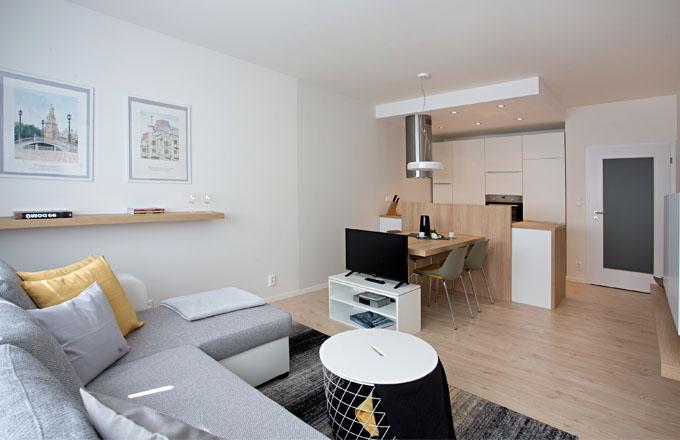 Pohodlná pohovka s televizí láká k relaxaci, jídelní stůl vytváří přechod ke kuchyňskému pracovišt