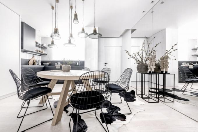 Kulatý jídelní stůl zhotovený na míru je doplněn kovovými židlemi (Pastoe) s čalouněním a skleněnými závěsnými svítidly (Lasvit)