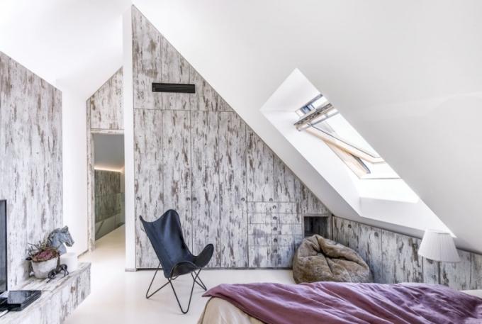 Podkrovní podlaží má stejně jako přízemní podlahu z lité béžové stěrky. Obě ložnice spojuje otevřená prosklená galerie