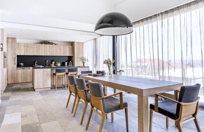 Velký jídelní stůl doplňují čalouněné židle (Ton) s područkami, které zajišťují pohodlí i při delším stolování. Nad stolem září oblíbené svítidlo Skygarden (Flos) s průměrem 90 cm