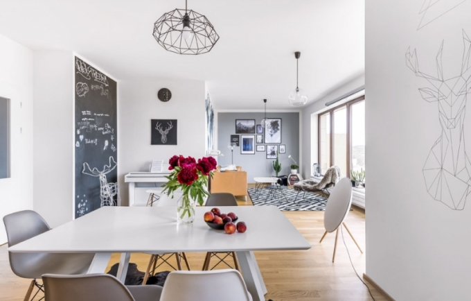 Hudební koutek s bílým pianinem zajímavě rámuje stěna ošetřená černou tabulovou barvou. Nechybí ani oblíbení parožnatci. Prostorem rytmicky prostupují geometrické prvky, které se vzájemně podporují – drátěné svítidlo, nástěnná kresba jelena, kterou vytvořila Eliška, nebo podnože židlí a stolků