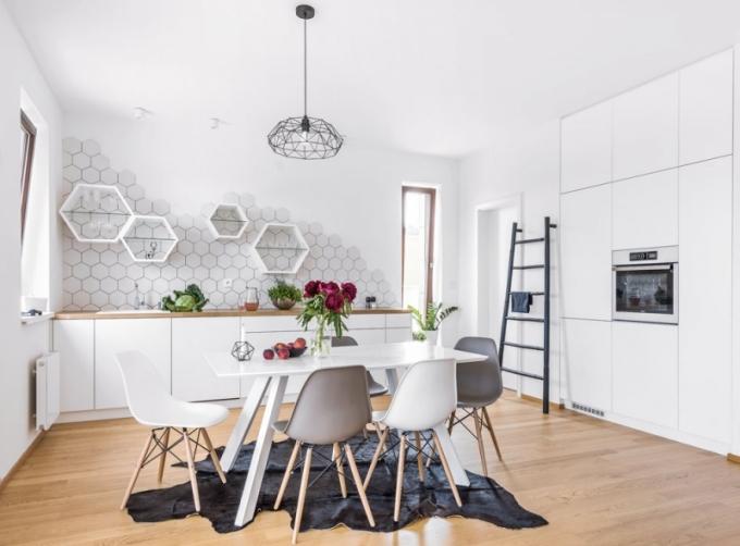 Kuchyňská sestava nábytku je autorským dílem designérky Markéty Fleischnerové. Je zhotovena z bíle lakované MDF desky, granitový dřez je zasazen do pracovní desky z dubového masivu. Skříňky ve tvaru hexagonů doplňují i obkládačky Tonalite (Siko) stejného tvaru. Bílý jídelní stůl zdobí legendární Eames DSW židle (Vitra). Na stěně se skvěle vyjímá jelen, kterého lihovou fixou narýsovala Eliška
