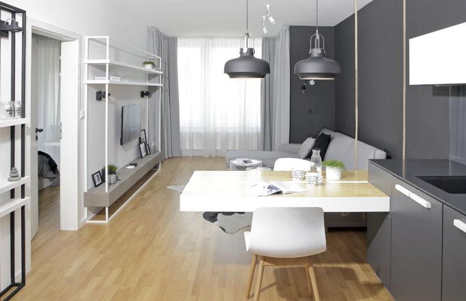Geometricky přesné jeklové konstrukce nábytku dodávají prostoru řád, který je v souladu s elegantním barevným schématem a celkovým pojetím interiéru v pánském stylu. Cementová stěrka pod televizí doplňuje závěsy a pohovku ve světlejších odstínech šedé