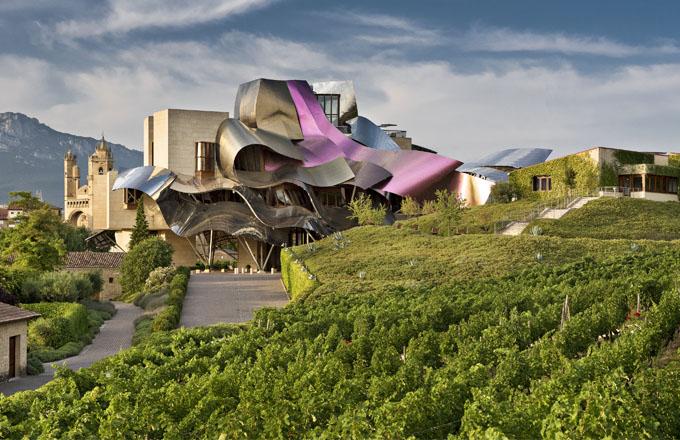 Když majitelé vinařství Marqués de Riscal oslovili Franka Gehryho s nabídkou na projekt centrály a hotelu, architektovi se do zakázky moc nechtělo. Nakonec jej spíš než honorář ve výši deseti milionů dolarů přesvědčil dárek z přísně střeženého trezoru v nejhlubším sklepení vinařství, kde se tradičně uchovává to nejlepší z každé sklizně už od roku 1859: zaprášená láhev s etiketou 1929, stejně stará jako sám Gehry