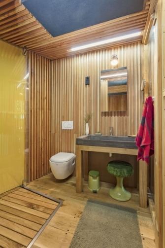 Koupelnu se sprchovým koutem bylo nutné vměstnat do atypicky zkoseného prostoru. Vytápění zde zajišťují kromě krbových kamen také sálavé panely