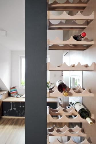 Atypická vinotéka opticky uzavírá kuchyňskou část. Matná tabulová barva oživuje řešení a s dekorem dřevěné dýhy vytváří příjemný kontrast