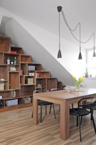 Masivní jídelní stůl je umístěný v obývací části. Prostor pod šikminou tu vyplňuje policový systém. Na nábytek je použitá dýha ve třech odstínech