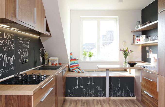 """Díky omyvatelné tabulové barvě může kuchyň měnit svou tvář. Kreslené dekorace autorek návrhu jí propůjčily. příjemně hravou podobu. Malý stolek """"vystupuje"""" z pracovní desky kuchyňské linky a slouží jako alternativa velkého jídelního stolu"""