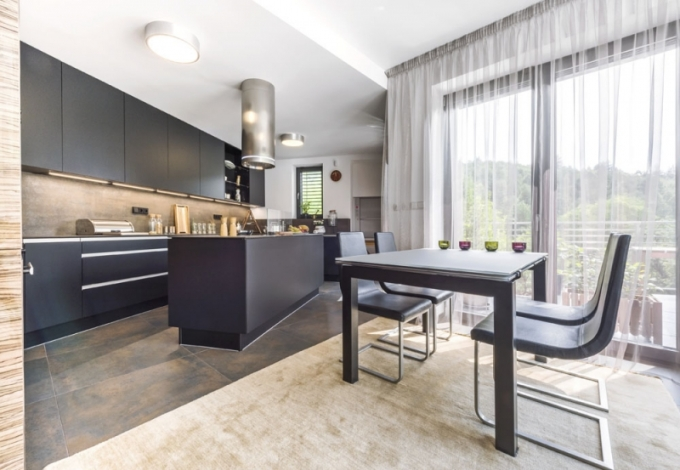 V prostoru plném přirozeného světla, které sem přichází velkými francouzskými okny, si majitel mohl dovolit kuchyňskou linku v moderním černém matu