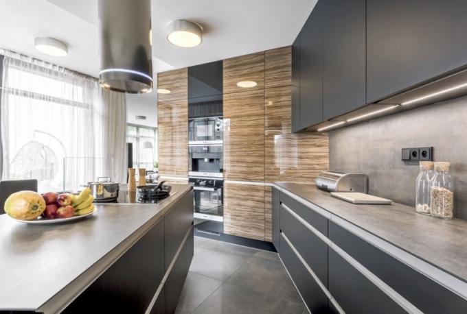 Lehce industriální nádech dodává kuchyni slinutá keramika se vzhledem ošoupaných kovových plátů, která je použitá na obkladech, dlažbě i pracovní desce