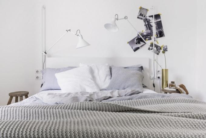 Bílou barvou upravenou postel (Ikea) s lněnými lůžkovinami po obou stranách zajímavě rámují výškově nastavitelné lampy (Lampe Gras) a stoličky z jilmového dřeva, které suplují noční stolky. Ložnice je také vybavena vestavnými skříněmi na míru