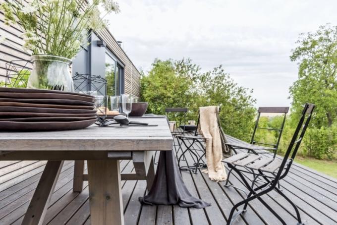 Na východní terase z modřínového dřeva kralují velký jídelní stůl (Ikea) a staré těžké skládací židličky, které architektku provázejí od dětství
