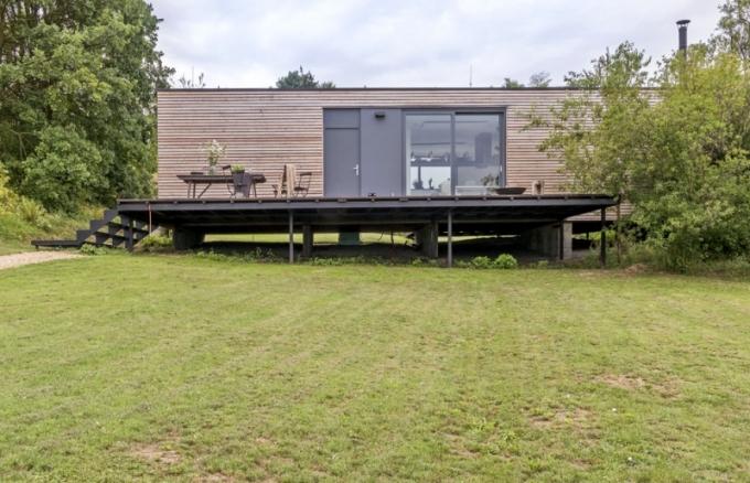 Mobilní dřevostavba z modřínového dřeva skvěle zapadá do zahrady, která přirozeně navazuje na okolní krajinu