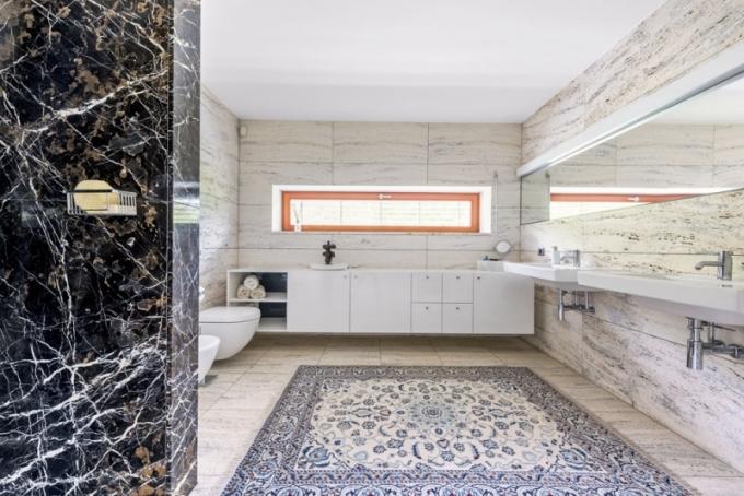 Velkorysá koupelna připomíná mramorový chrám, kde je rozprostřen pomněnkově modrý perský koberec. Sprchový kout je odlišen mramorem Africano. Umyvadla (Villeroy & Boch) jsou doplněna bateriemi Dornbracht a skříňka je zhotovená na míru z lakované MDF desky