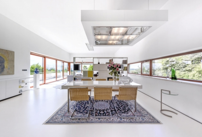 Jídelnu částečně vymezuje velmi hustě tkaný perský vlněný koberec (vyrobený v Íránu), laděný do modrých tónů. Jídelní stůl (270 x 100 cm) na nerezových nohách, zhotovený z MDF desky lakované do vysokého lesku, obklopuje šest designových ikon – židlí v ratanové verzi od architekta a designéra Ludwiga Miese van der Rohe