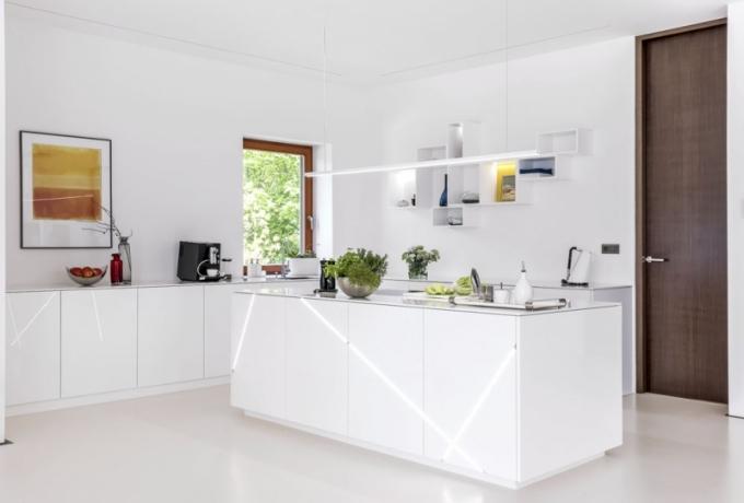 Bílou kuchyň oživují akcenty černé, dijonské žluté a zajímavě instalované osvětlení. Je vybavena spotřebiči Siemens