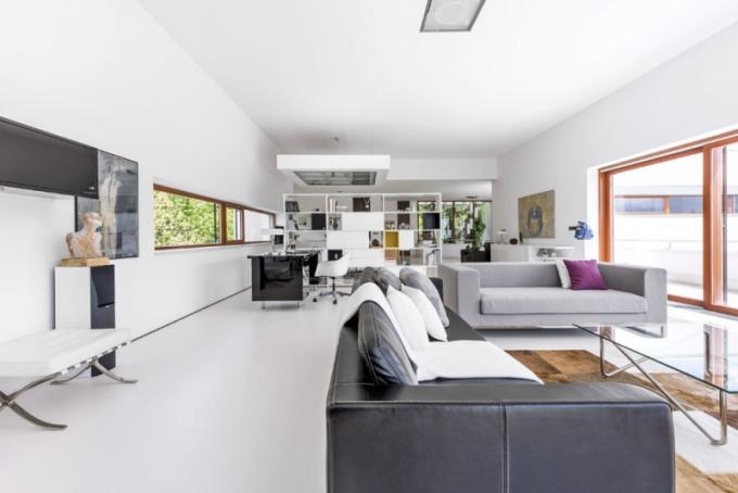 Pohodlné usednutí v obývacím pokoji nabízejí dvě pohovky, kožená (Classic Leather) a textilní (Antonio Citterio) a dvě kožená ikonická křesla Barcelona. Skleněný stolek navrhl architekt a je postaven na koberci (Arne Jacobsen) zhotoveném z kožešin. Komoda v bílém rámu s černým opálovým sklem je inspirovaná stylem Ludwiga Miese van der Rohe. Černý akcent v převažující záplavě bílé barvy vytváří i psací stůl