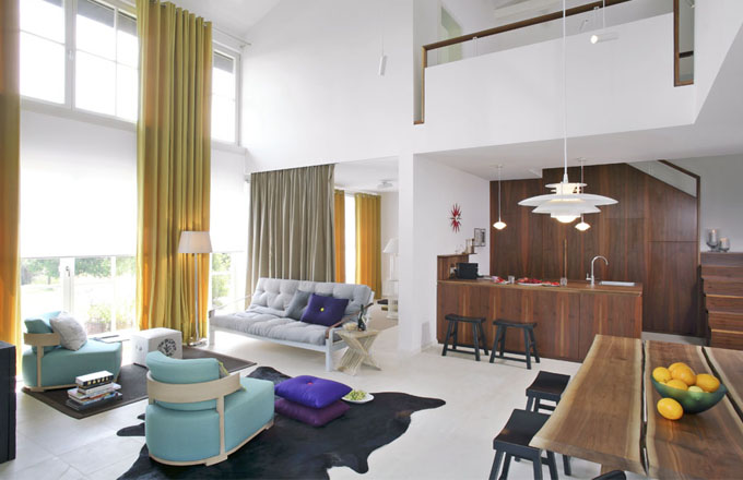 Společný obývací prostor je orientován na jih do zahrady. Jeho součástí je i pokoj pro hosty, oddělený jen závěsem. Sedací nábytek je kombinací futonu a sedacích vaků pushbag, které je možné použít i v exteriéru