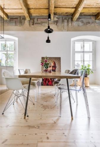 Masivní dubový jídelní stůl ze tří fošen na kovové podnoži je designovou lahůdkou českých designérů ze studia Vjemy. Odstraněné dřevěné suky na povrchu desky jsou vyplněny cínem. Obklopují ho plastové ikonické židle značek Vitra a Kartell