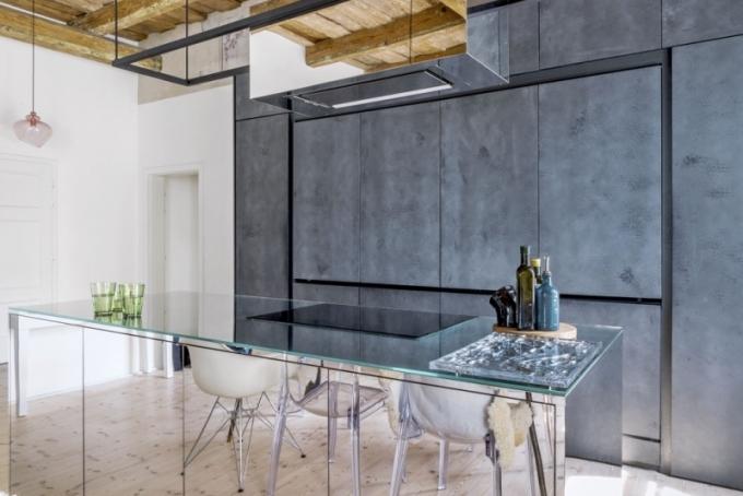 Kuchyňský nábytek je zhotoven podle autorského návrhu architektů z nevšedního materiálu zv. of stone – černého betonu aplikovaného na MDF desku. Součástí kuchyně je velký ostrůvek vybavený indukční varnou deskou a troubou, jehož útroby lze využívat přístupem z obou stran. Je zhotovený ze speciálně leštěného nerezového kovu se zrcadlovým efektem. Stejným materiálem je povrchově upravena i digestoř, která v tomto provedení ztrácí opticky svoji hmotnost