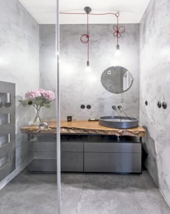 Stěny koupelny jsou ošetřeny epoxidovou stěrkou Betonepox (Němec). Deska pod umyvadlo je z lakované kořenovice africké dřeviny. Na ní je posazeno betonové umyvadlo (Gravelli)