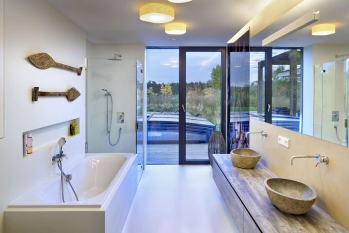 I v koupelně architekti mysleli na propojení vnitřního prostoru s exteriérem zahrady. Moderní bílou koupelnu doplňují kamenná umyvadla navozující wellness atmosféru