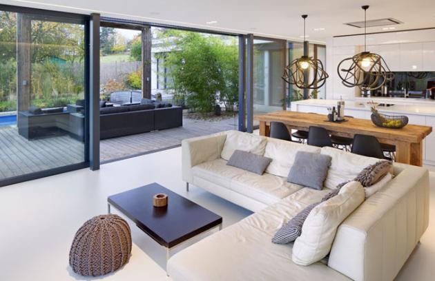 Celý prostor domu opticky zvětšují velké prosklené plochy a bílá litá stěrka na podlaze, poznávací znamení domů Ateliéru Kunc Architects