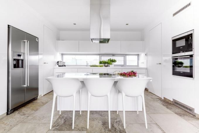 Běloskvoucí dojem interiéru umocňuje bílý nábytek, například polykarbonátové židle Dr. Yes designéra Philippa Starcka a podle Kamilina návrhu na míru zhotovená kuchyň z MDF desky lakované do vysokého lesku. Bílá je i pracovní deska z umělého kamene, která plynule navazuje na dřez ze stejného materiálu. Kuchyň je vybavena spotřebiči Siemens včetně velké americké chladničky s výrobníkem ledu