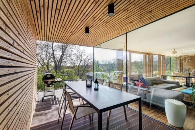 Krytá terasa vedle obývacího pokoje poskytuje příjemný prostor pro venkovní stolování s grilováním, chráněný před sluncem, větrem i deštěm. Bonusem je krásný výhled do okolí.
