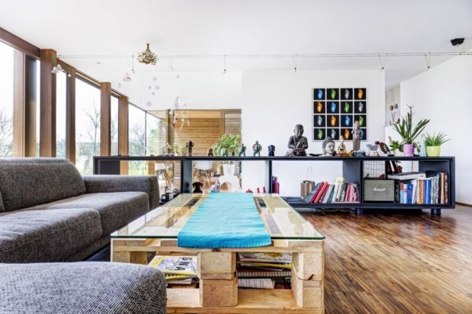 Společný obývací prostor je rozdělen na sezení a kuchyňskou část, skrytou za polopříčkou. Středem prochází schodiště ze spodního podlaží, lemované dlouhou otevřenou skříňkou z MDF desek a černého ocelového plechu.