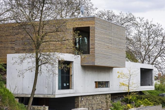 Obklad fasády ze střešních latí opticky člení velký objem horního podlaží. Časem získá šedavou patinu a přirozeně se zapojí do prostředí.
