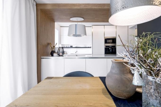 Kuchyň v nadčasové bílé barvě je značky Sykora model Exclusive v provedení bílá v matném laku, pracovní deska je z materiálu Technistone, nad ostrůvkem trůní odsavač par kombinovaný s čističkou vzduchu Falmec
