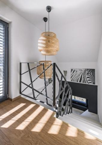 Kovové schodiště vyrobené na zakázku je z jednoho kusu kovu a vede od sklepa, přes přízemí až do patra domu. Podle majitelčina návrhu ho vyrobil umělecký kovář
