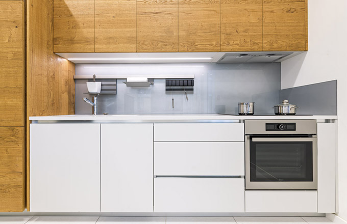 Ve svých showroomech se na kuchyňských sestavách snaží společnost JN Interiér prezentovat různé materiály, aby si je zákazníci mohli prohlédnout a vyzkoušet, zda jim jsou na omak příjemné. Tato kuchyň je sestavená z kombinace lamina v super matném provedení a dubové dýhy s drásaným povrchem