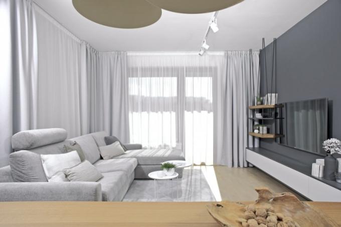 Nábytek v obývacím pokoji je zhotovený na míru. Bylo použito matné lamino a dubová dýha, která polyfunkční celek propojuje s jídelnou a kuchyní. Pohovku doplňují polštáře (Deconcept) a hnízdové stolky Cartagena (BoConcept). Světlešedé textilie - koberec, závěsy i čalounění rozkládací sedací soupravy (Nadop) vhodně doplňují barevný koncept interiéru a podporují jeho vzdušnost
