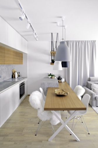 Jídelní stůl z dubové dýhy volně navazuje na kuchyňský ostrůvek a přechází v praktické police