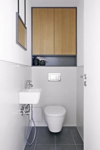 Ani WC místnost s klozetem (Ideal Standard), bidetovou sprškou (Oras) a s malým umyvadlem (Laufen) nenarušuje barevně a materiálově jednotný koncept interiéru