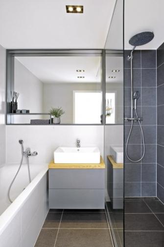 Do koupelny se vešla akrylátová vana (Riho) a na přání majitelů i velkorysý sprchový kout vybavený bateriemi Hansgrohe. Je obložena keramickou dlažbou formátu 60 x 30 cm. Optickému zvětšení místnosti napomáhá velké zrcadlo s odkládacím prostorem. Umyvadlo (Ideal Standard) se dočkalo skříňky na míru podle návrhu studia Martina Design