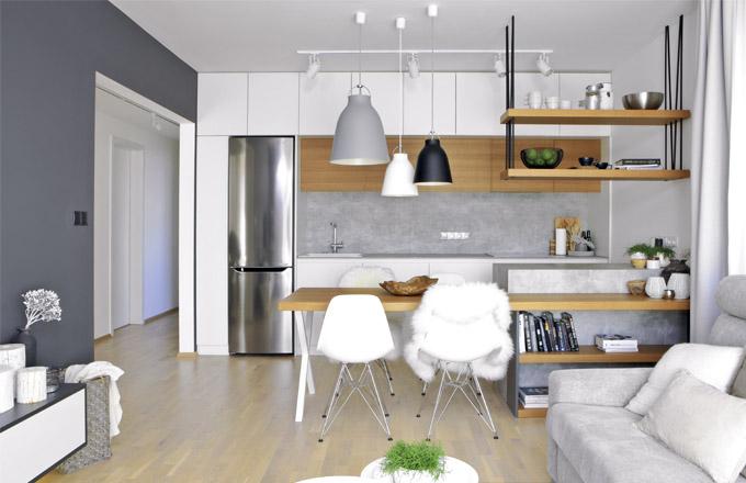 Kuchyňská sestava nábytku je zhotovená na míru s využitím maximální výšky místnosti i z důvodu většího množství úložných prostorů. Barevný koncept interiéru podporují také bílý dřez (Franke) a indukční varná deska. Kromě volně stojící nerezové chladničky (LG) je kuchyň vybavena vestavnými spotřebiči Bosch. Ostrůvek a obklad za pracovní deskou je vyroben z HPL desky připomínající betonový povrch
