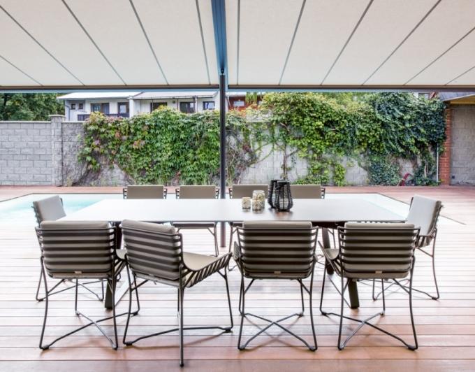 Pohodlí na terase zajišťuje kvalitní kovový stůl a židle z kolekce Hamptons a venkovní lůžko Day beds (obojí Roberti Rattan)