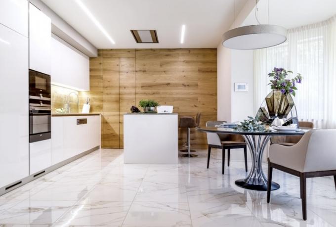 Nyní je kuchyň víc otevřená, přitom kompaktní a praktičtěji řešená s prostorným varným ostrůvkem, který plní i funkci barového stolu. Je zhotovená z bíle lakované MDF desky, v kombinaci s kouřovým dubem působí lehce. Pracovní deska je z materiálu Technistone a stěna za ní je chráněná kaleným sklem. Arkýř domu poskytuje vhodné místo jídelně. Je vybavena velkým skleněným stolem Radar (Alivar), kam může pohodlně do kožených křesílek Marilyn (MIDJ) usednout až osm osob