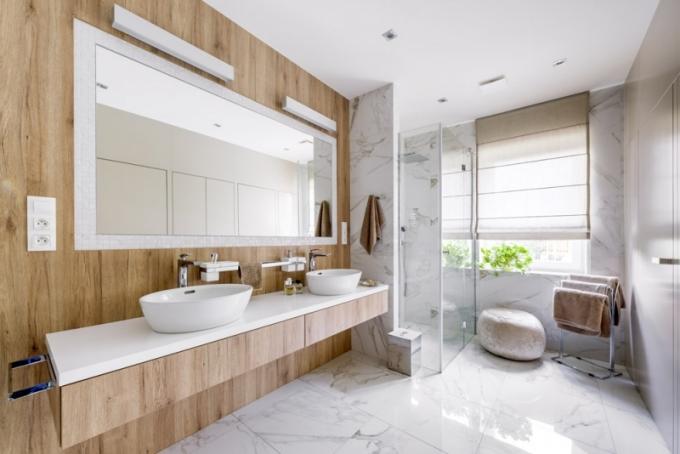 Koupelna v přízemí s dvěma umyvadly (Laufen) posazenými na desce z corianu a doplněnými bateriemi Kludi má nenápadnou stěnou s bezfalcovými dveřmi oddělený klozet, prádelnu a úložné prostory