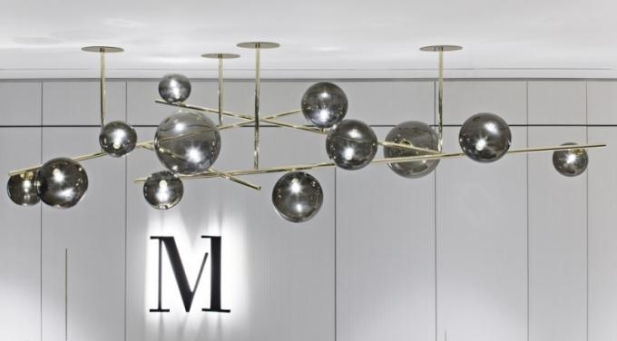 Závěsná světelná plastika vytvořená na míru pro lobby objektu Millennium, trubková konstrukce z leštěné mosazi doplněná o 12 ručně foukaných skleněných koulí, 240 x 120 cm