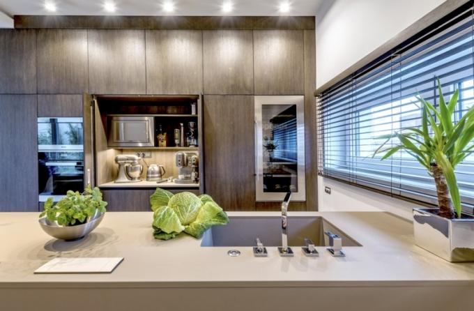 Kuchyňský ostrůvek (Ernestomeda) z materiálu Fénix povrchovou úpravu s nanotechnologií pro snazší údržbu. Je kombinovaný s nábytkem zhotoveným na míru, který připomíná dřevěný box. Nábytkový modul je vyrobený z dubu mořeného do odstínu wengé. Lze ho otevřít a využít tak další pracovní prostor a spotřebiče umístěné uvnitř. Součástí ostrůvku Ernestomeda jsou také dřez a baterie Franke