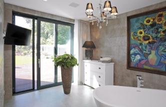 Atmosféru budoáru dodává relaxační části koupelny i křišťálový lustr a skříňka se stolní lampou