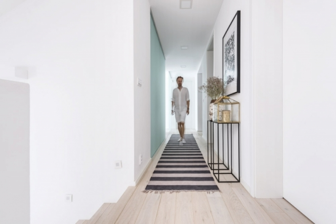 Šatnu od vstupní chodby oddělují skleněné posuvné dveře s rustikálními dřevěnými úchyty, které jsou designově propojeny s dřevěnými věšáky v šatně