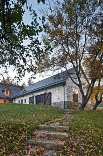 Chalupa a stodola umístěné do tvaru L jsou harmonicky posazené do svažité louky