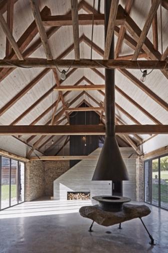 """Velkorysý prostor stodoly je otevřený až do krovu. Jeho dominantu tvoří tmavá """"věž"""" a stěna před ní vymezující schodiště. Zhotovena je z betonu, který zjemňuje textura vzniklá otiskem dřevěných prken. Kamenné zdivo, cihlové klenby v části s patrem a ve sklepě i krov jsou zde původní"""